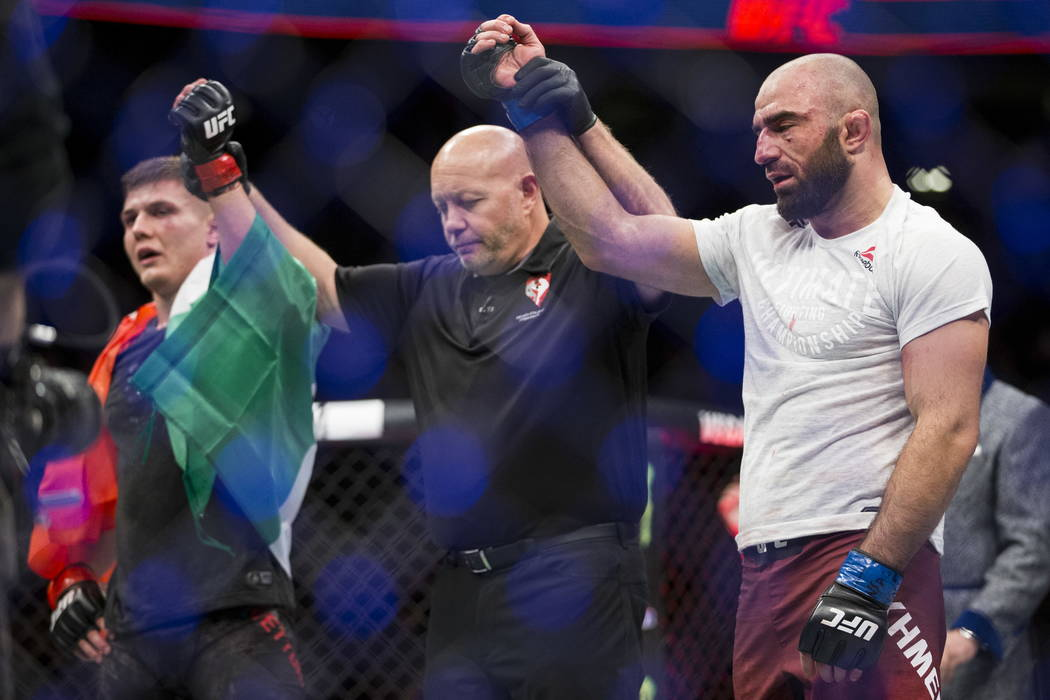 Marvin Vettori, left, and Omari Akhmedov raise their hands after a split draw was announced in the UFC 219 middleweight bout at T-Mobile Arenain Las Vegas, Saturday, Dec. 30, 2017. Erik Verduzco/L ...