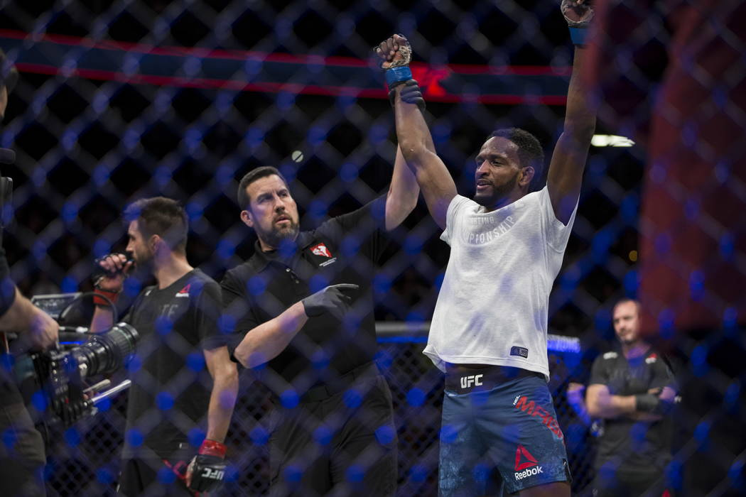 Neil Magny, right, is announced the winner against Carlos Condit in the UFC 219 welterweight bout at T-Mobile Arena in Las Vegas, Saturday, Dec. 30, 2017. Magny won by unanimous decision. Erik Ver ...