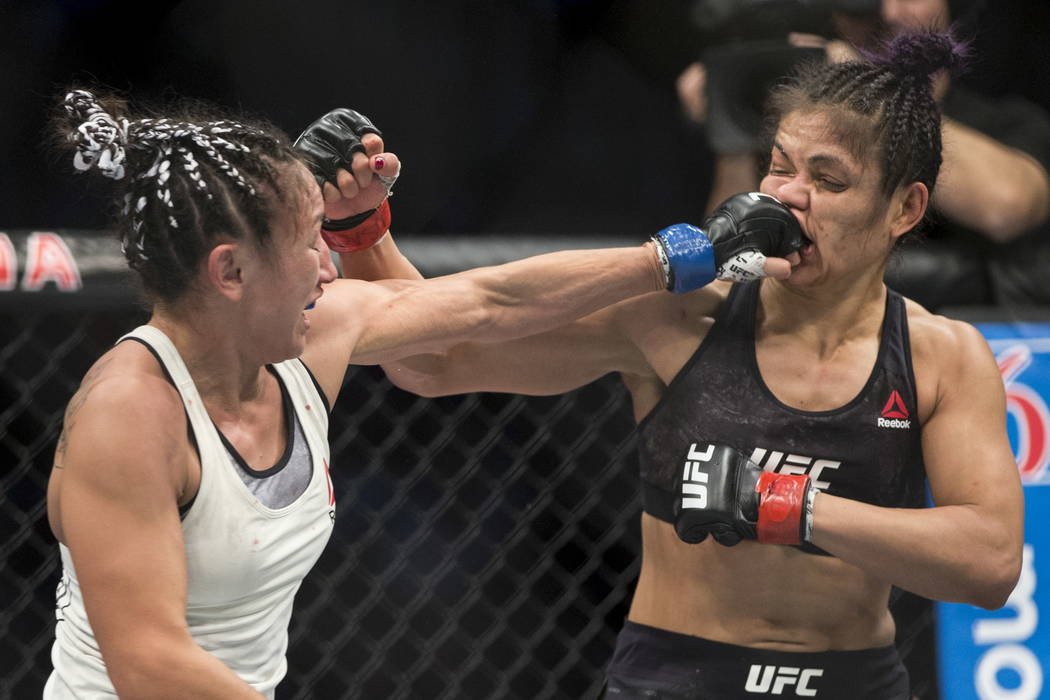 Carla Esparza, left, connects a punch against Cynthia Calvillo in the UFC 219 women's strawweight bout at T-Mobile Arena in Las Vegas, Saturday, Dec. 30, 2017. Esparza won by unanimous deci ...