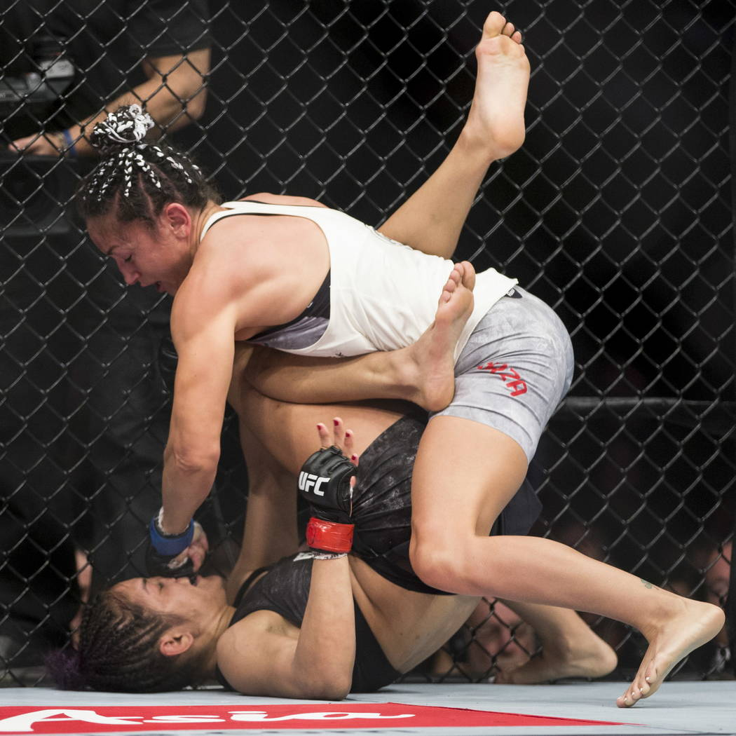 Cynthia Calvillo, bottom, takes a punch against Carla Esparza in the UFC 219 women's strawweight bout at T-Mobile Arena in Las Vegas, Saturday, Dec. 30, 2017. Esparza won by unanimous decis ...
