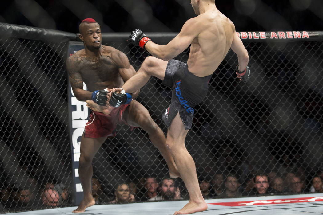 Marc Diakiese, left, battles Dan Hooker in the UFC 219 lightweight bout at T-Mobile Arena in Las Vegas, Saturday, Dec. 30, 2017. Hooker won by way of submission in the third round. Erik Verduzco/L ...