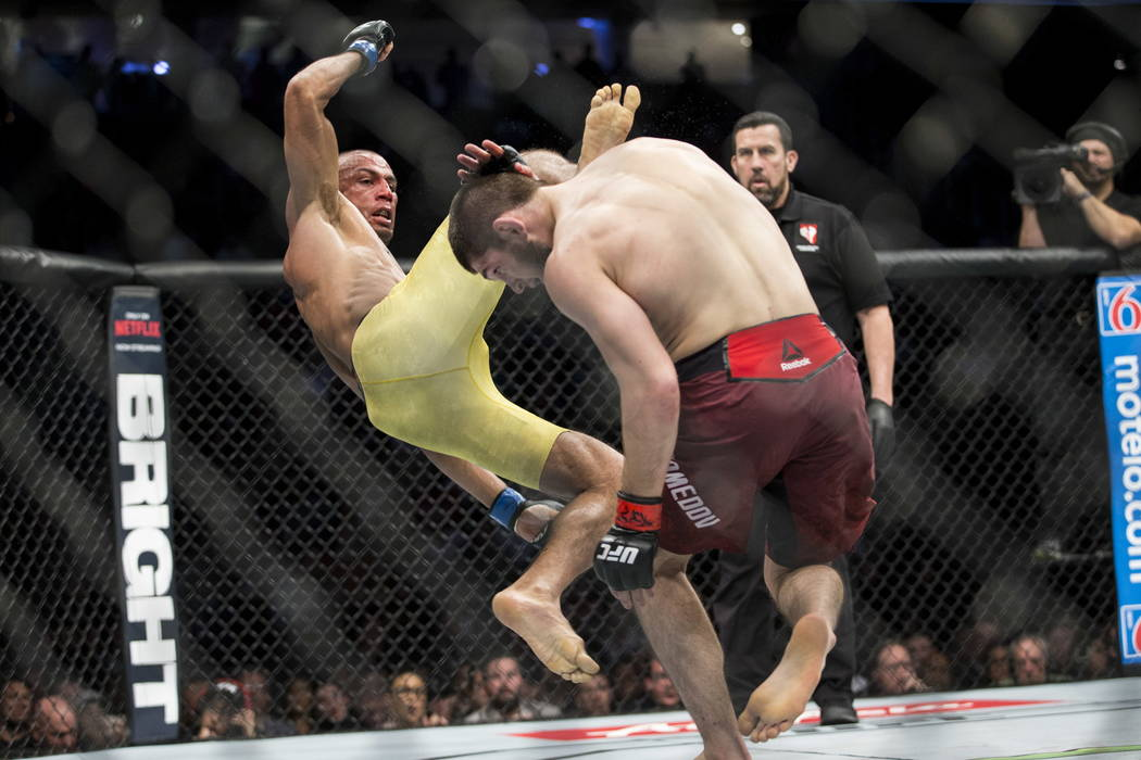 Edson Barboza, left, leaps for a kick against Khabib Nurmagomedov in the UFC 219 lightweight bout at T-Mobile Arena in Las Vegas, Saturday, Dec. 30, 2017. Nurmagomedov won by unanimous decision. E ...