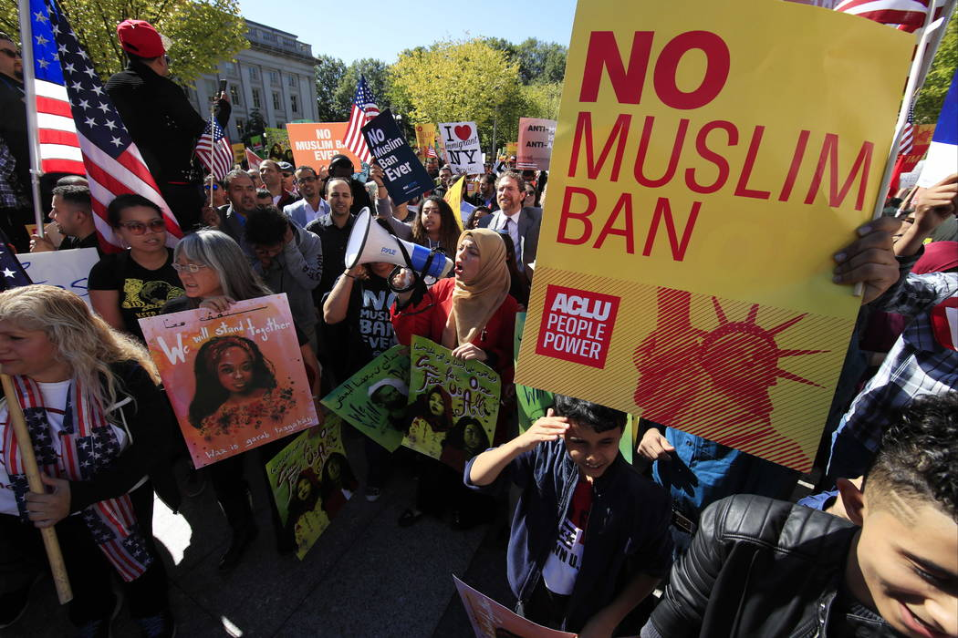 FILE - In this Oct. 18, 2017, file photo, protesters gather at a rally in Washington. The Supreme Court is allowing the Trump administration to fully enforce a ban on travel to the United States b ...