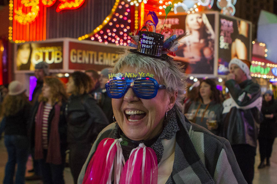"Julie Witts from Canada listens to a Billy Idol tribute band during the ""Downtown Countdown"" at Fremont Street Experience on Wednesday, Dec. 31, 2014. Revelers are ringing in the new ..."
