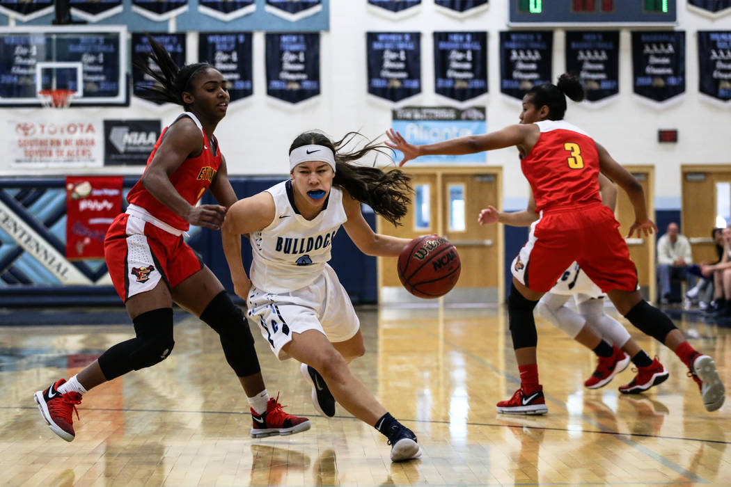 Centennial's Melanie Isbell (2) dribbles the ball past Etiwanda's Aujane Mayes (2) during the first quarter of the Las Vegas Holiday Classic championship basketball game at Centennial High School  ...