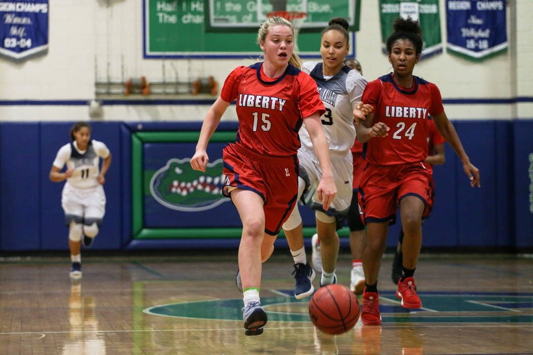 Liberty's London Pavlica (15) dribbles the ball past Spring Valley's Alexus Quaadman (23) and Liberty's Trinity Vasquez (24) during the second quarter of the championship basketball game of ...