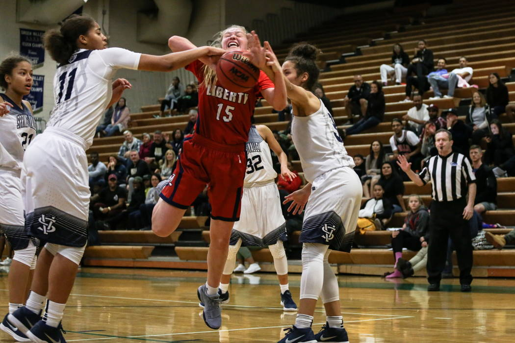 Liberty's London Pavlica (15) is blocked by Spring Valley's Kayla Harris (11) and Essence Booker (3) during the second quarter of the championship basketball game of the diamond bracket in  ...