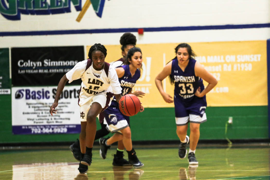 Cimarron-Memorial's Chynna Torrence (12) dribbles the ball past Spanish Springs' Naelia Pinedo (11) and Spanish Springs' Madlyn Winters (33) during the first quarter of a basketball game during th ...