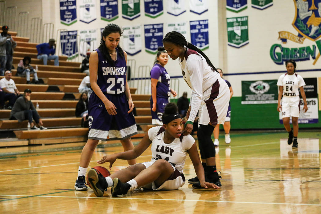 Spanish Springs' Serena Sanchez (23) watches as Cimarron-Memorial's Amoura Whitney (33) helps pick up teammate Tasia Moore (34) during the first quarter of a basketball game during the Gator Winte ...