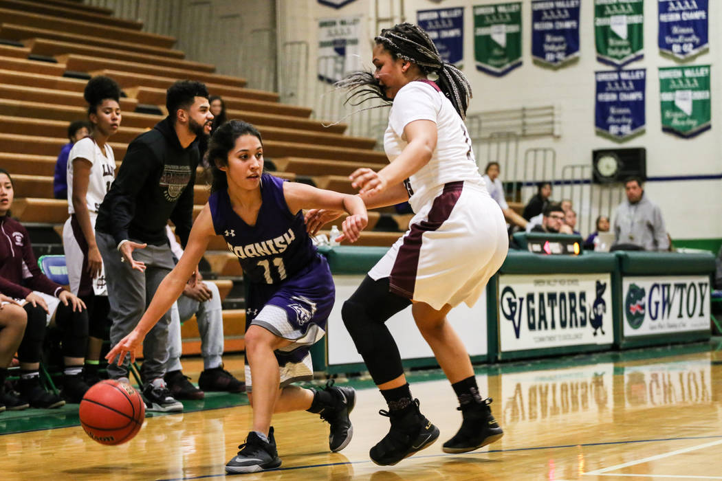 Spanish Springs' Naelia Pinedo (11) dribbles the ball as she is guarded by Cimarron-Memorial's Elise Young (1) during the second quarter of a basketball game during the Gator Winter Classic at Gre ...
