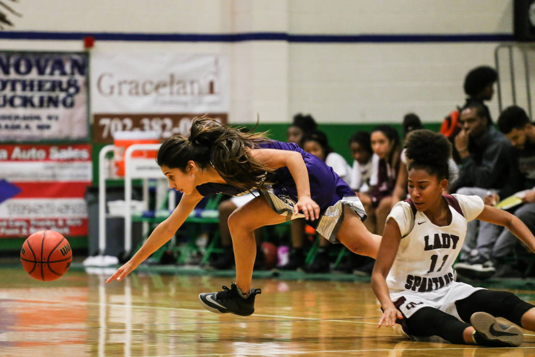 Cimarron-Memorial's Mary-Jane Williams-Law (11) watches as Spanish Springs' Naelia Pinedo (11) leaps for a loose ball during the fourth quarter of a basketball game during the Gator Winter Classic ...