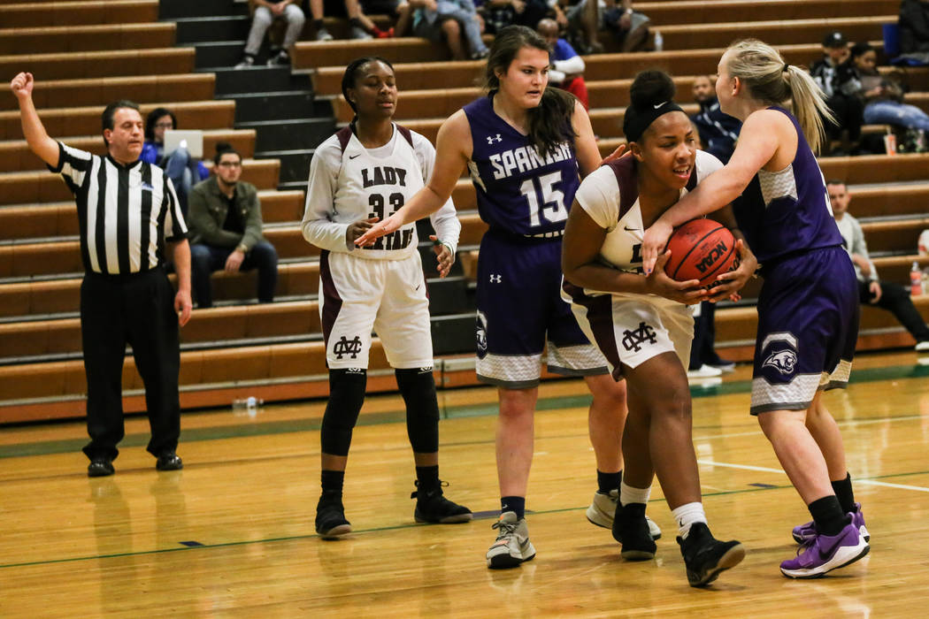 Cimarron-Memorial's Tasia Moore (34), left, holds onto the ball as Spanish Springs' Megan Gower (5) tries to take it during the fourth quarter of a basketball game during the Gator Winter Classic  ...