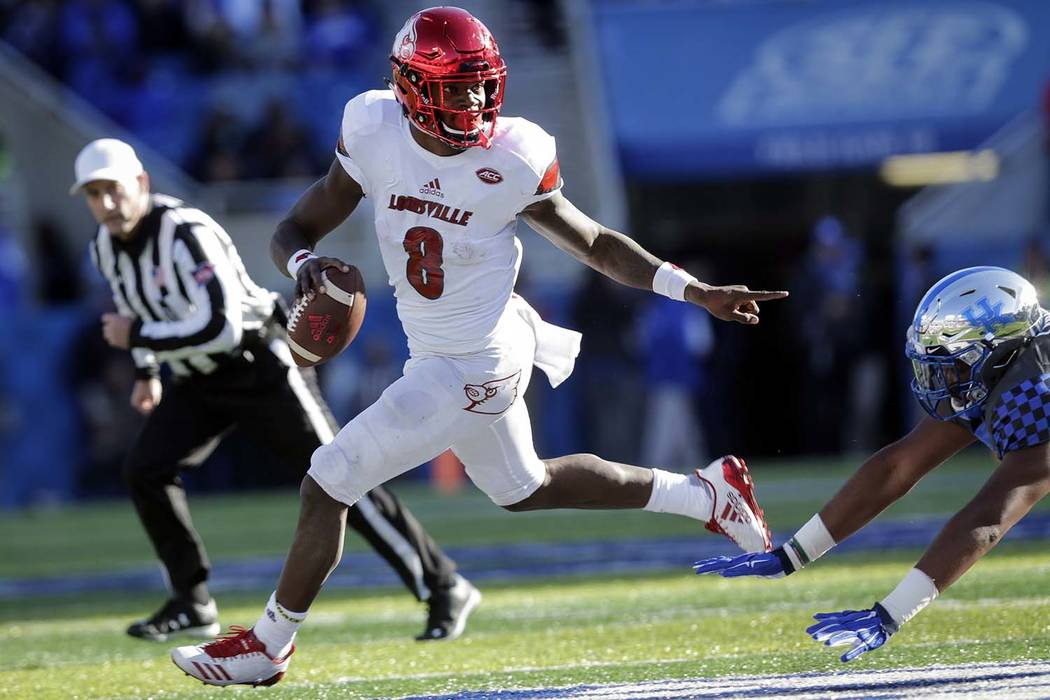 In this Nov. 25, 2017, file photo, Louisville quarterback Lamar Jackson (8) scrambles past Kentucky defensive tackle Kordell Looney during the second half of an NCAA college football game in Lexin ...