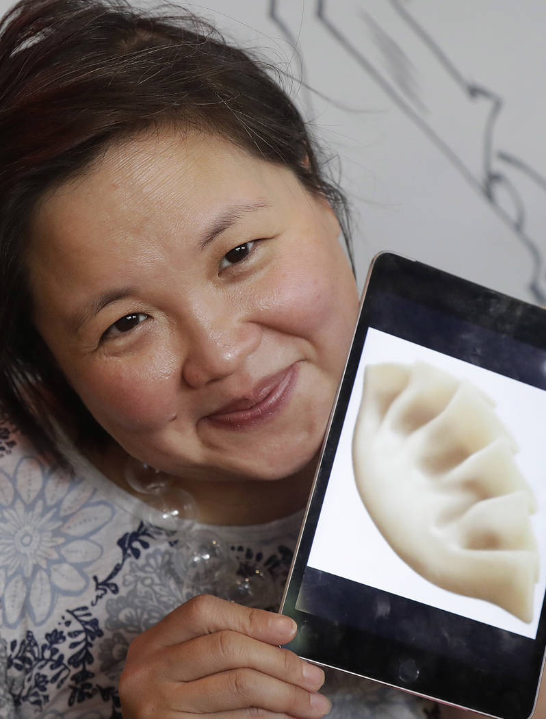 Author Jennifer 8. Lee holds an image of a dumpling emoji while posing for photos before eating lunch at Dumpling Time restaurant in San Francisco on Wednesday, Dec. 27, 2017. Thanks largely to Le ...
