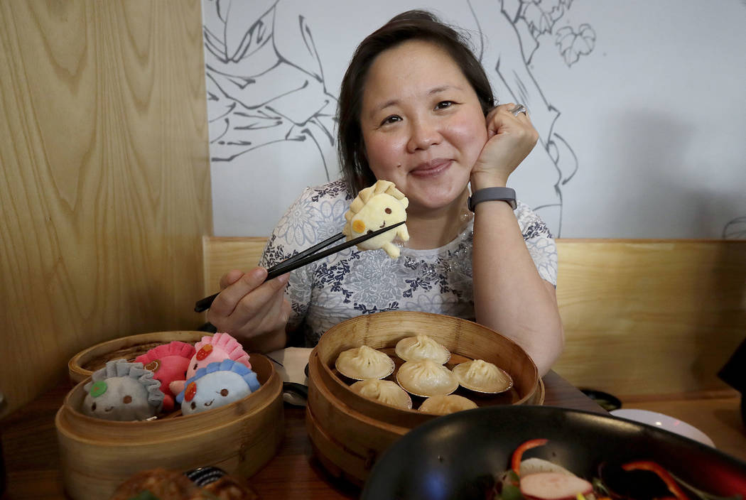 Author Jennifer 8. Lee poses for photos before eating lunch at Dumpling Time restaurant in San Francisco on Wednesday, Dec. 27, 2017. (AP Photo/Jeff Chiu)