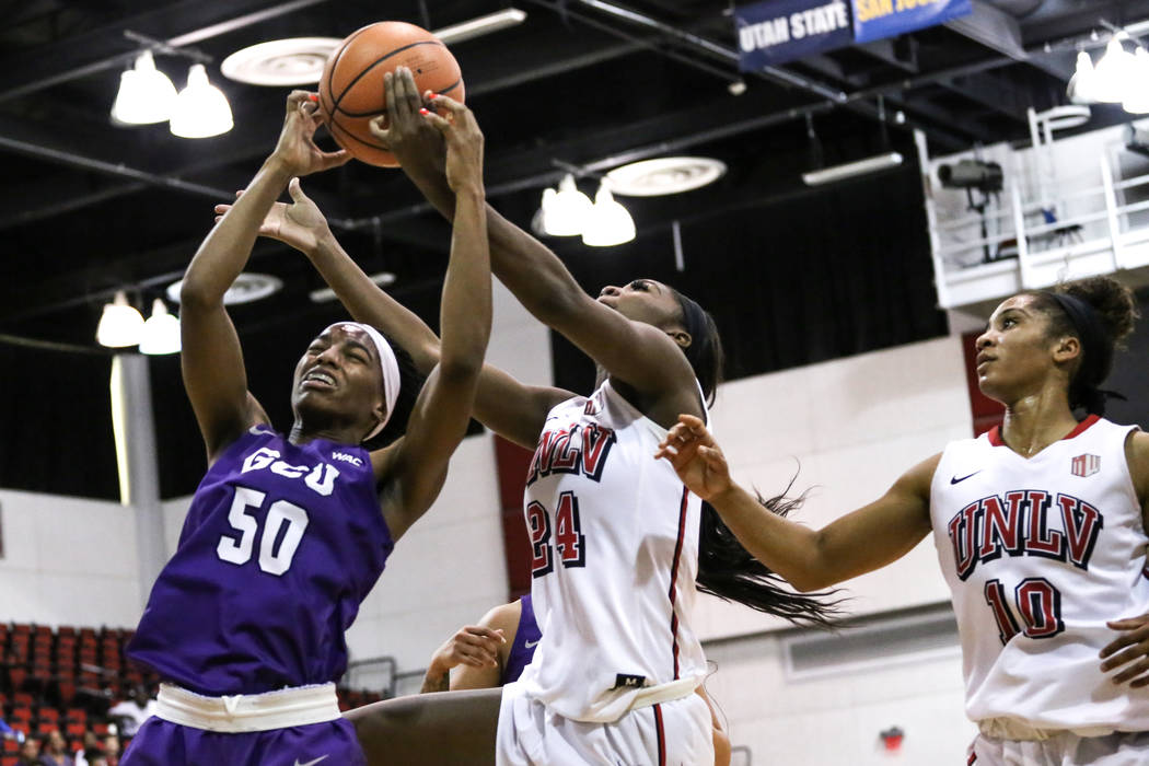 Grand Canyon Antelopes forward Myra Williams (50), left, and UNLV Lady Rebels center Rodjanae Wade (24), center, jump for the ball during second quarter of a basketball game at Cox Pavilion in Las ...