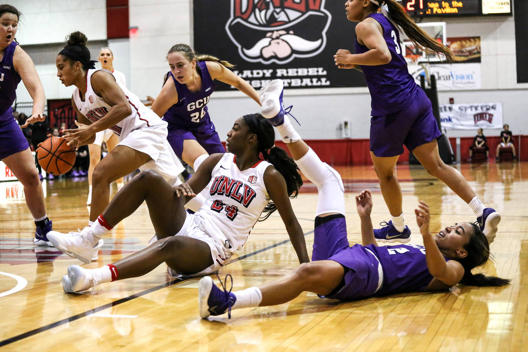 UNLV Lady Rebels center Rodjanae Wade (24), center, and Grand Canyon Antelopes guard August Touchard (2), right, hit the floor during third quarter of a basketball game at Cox Pavilion in Las Vega ...