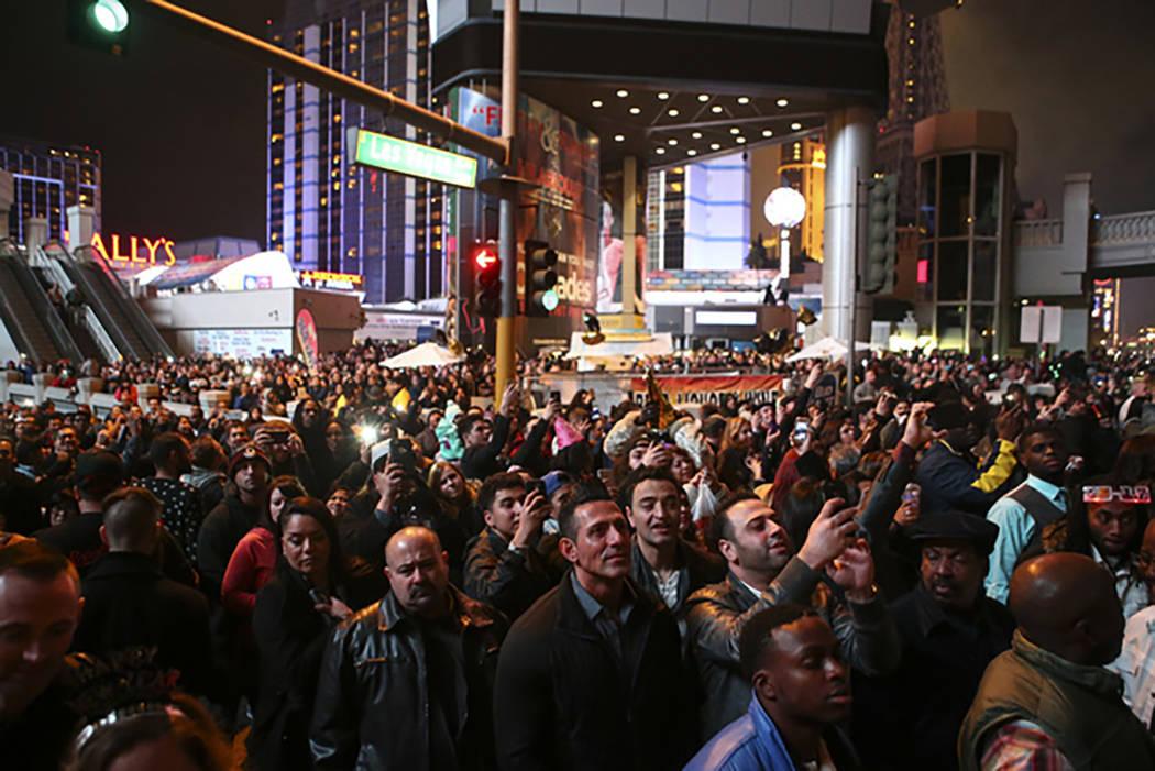 Fireworks go off as New Year's Eve revelers celebrate on the Las Vegas Strip on Sunday, Jan. 1, 2017. (Chase Stevens/Las Vegas Review-Journal) @csstevensphoto