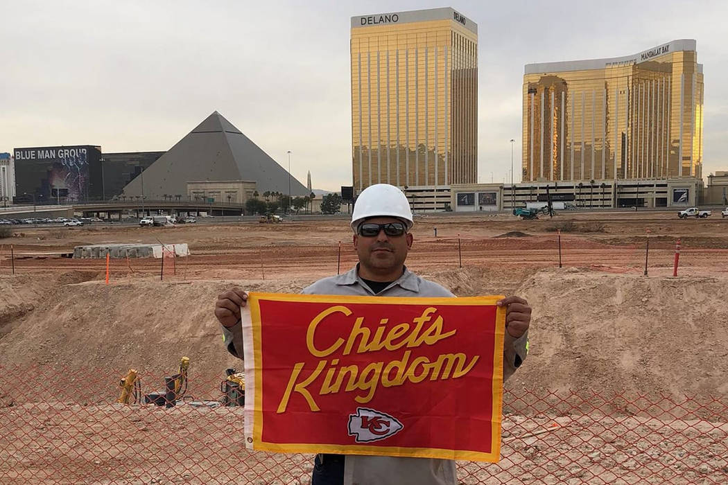 "A Chiefs fan named Chris Scherzer posted a photo of a man wearing a white hardhat and dark glasses and holding a red and gold Chiefs banner with the inscription ""Chiefs Kingdom"" on his Faceboo ..."