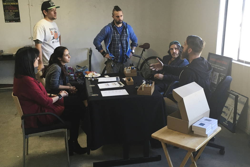 "Estrella Terrones, left, a ""budtender"" listens to a sales tutorial from one of the marijuana dispensary's suppliers at Golden State Greens marijuana dispensary in San Diego on Wednesday.  (AP Phot ..."