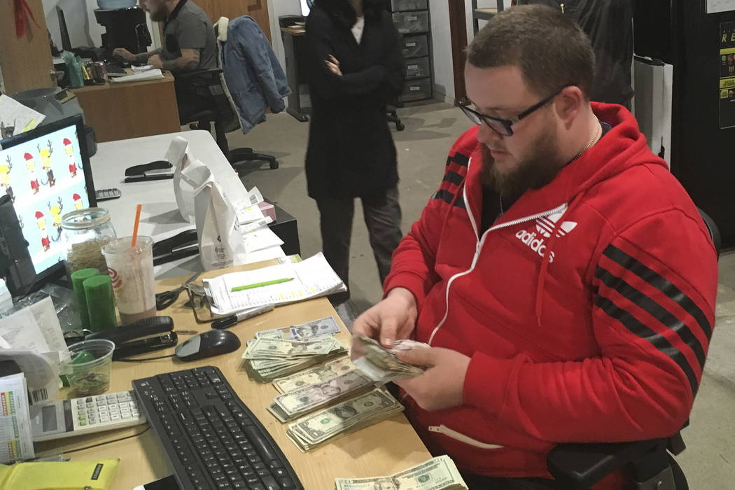 Employee Joshua Wilson counts cash at the Golden State Greens marijuana dispensary in San Diego on Wednesday. (AP Photo/Elliot Spagat)