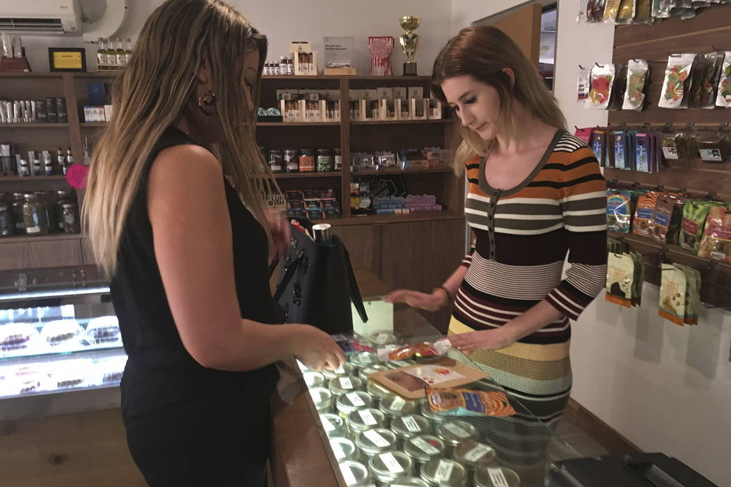 "Golden State Greens ""budtender"" Olivia Vugrin, right, waits on a customer in San Diego on Wednesday. (AP Photo/Elliot Spagat)"