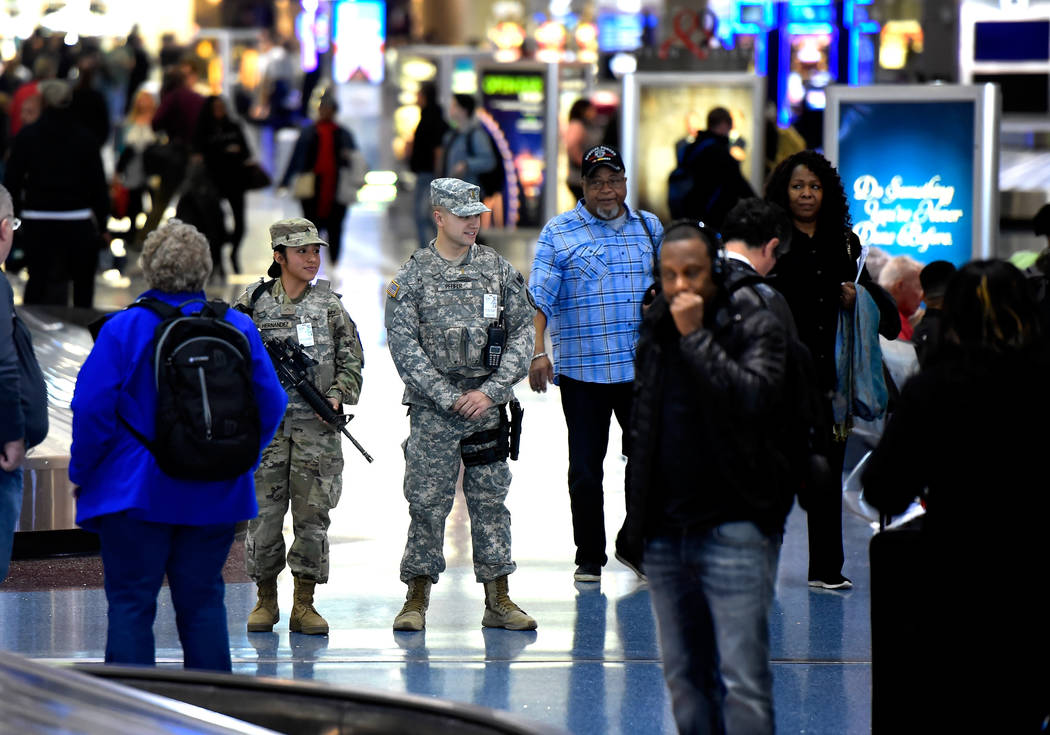 Pvt. Kimberly Hernandez, second left, and 2nd Lt. Drake Pfeifer of the 72nd Military Police company, patrol Terminal 1 baggage claim at McCarran International Airport Friday, Dec. 29, 2017, in Las ...