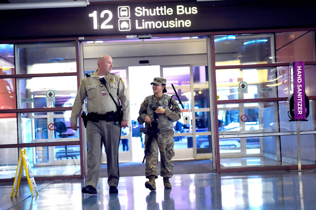Las Vegas police and a member of the Nevada Army National Guard patrol Terminal 1 baggage claim at McCarran International Airport Friday, Dec. 29, 2017, in Las Vegas. Over 300 soldiers and airmen  ...