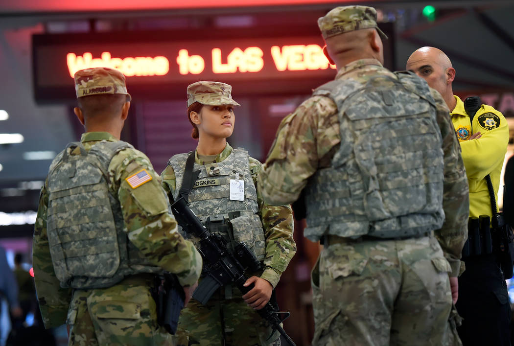 Las Vegas police and members of the Nevada Army National Guard patrol the Terminal 1 baggage claim at McCarran International Airport Friday, Dec. 29, 2017, in Las Vegas. Over 300 soldiers and airm ...