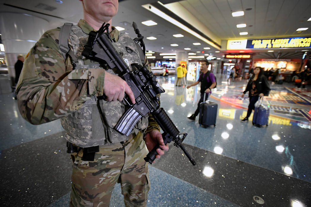 Staff Sgt. Kris Hayman of the Nevada Army National Guard carries his M-4 rifle as he patrols the Terminal 1 baggage claim at McCarran International Airport Friday, Dec. 29, 2017, in Las Vegas. Ove ...