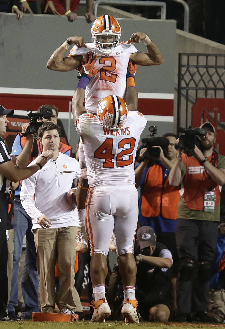 Clemson's Christian Wilkins (42) lifts quarterback Kelly Bryant (2) following Bryant's touchdown against North Carolina State during the second half of an NCAA college football game in Raleigh, N. ...