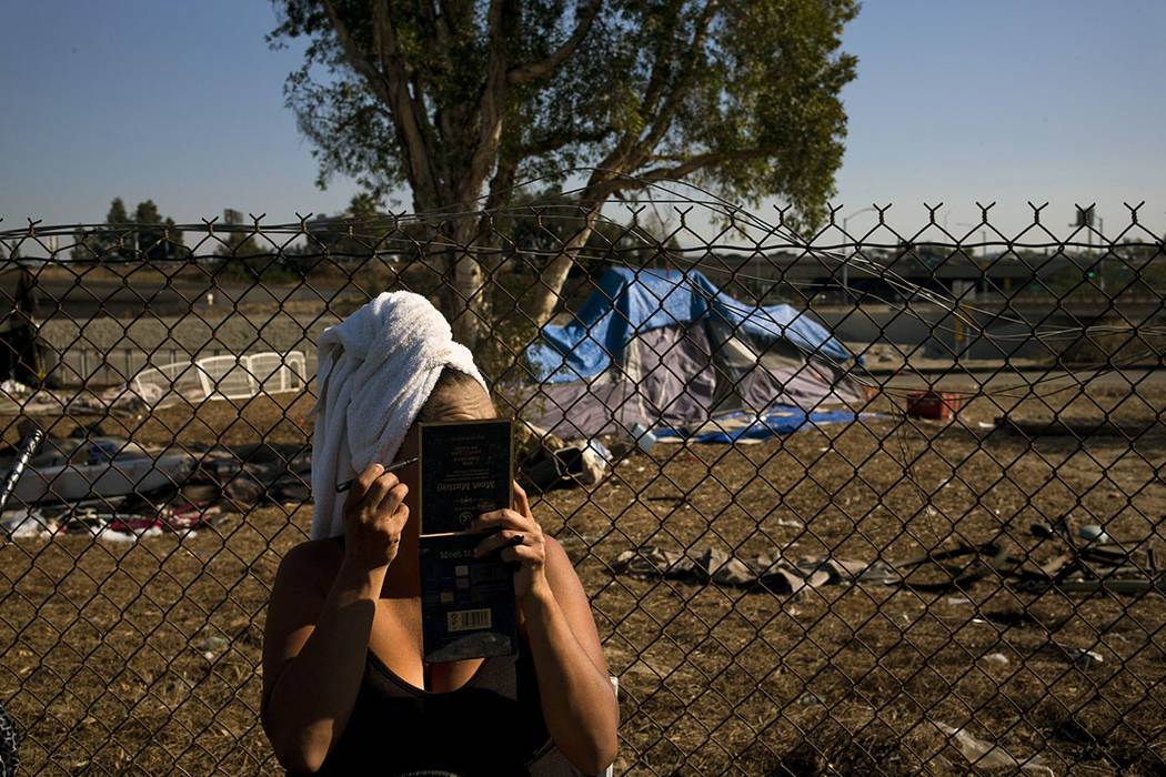 With a towel wrapped around her head, Stella Perez, who is homeless, applies makeup in the parking lot of Angel Stadium after taking a shower in Showers of Blessing, a mobile shower trailer built  ...