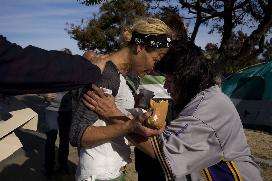 Amy Potter, left, and Victoria Pena, who are both homeless, pray for each other while holding donuts and coffee donated by local church members in a homeless encampment on the Santa Ana River trai ...