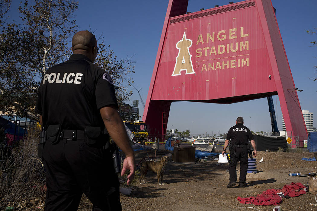 Two police officers, Eric Meier, right, and Curtis Bynum from the Anaheim Police Department's homeless outreach team walk through a homeless encampment set up outside Angel Stadium to hand out fly ...