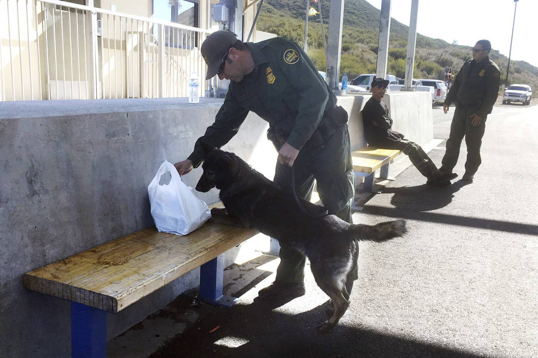 A drug sniffing dog discovers a small amount of marijuana in a bag at California's Pine Valley checkpoint, on the main route from Arizona to San Diego. (Elliot Spagat/AP Photo)
