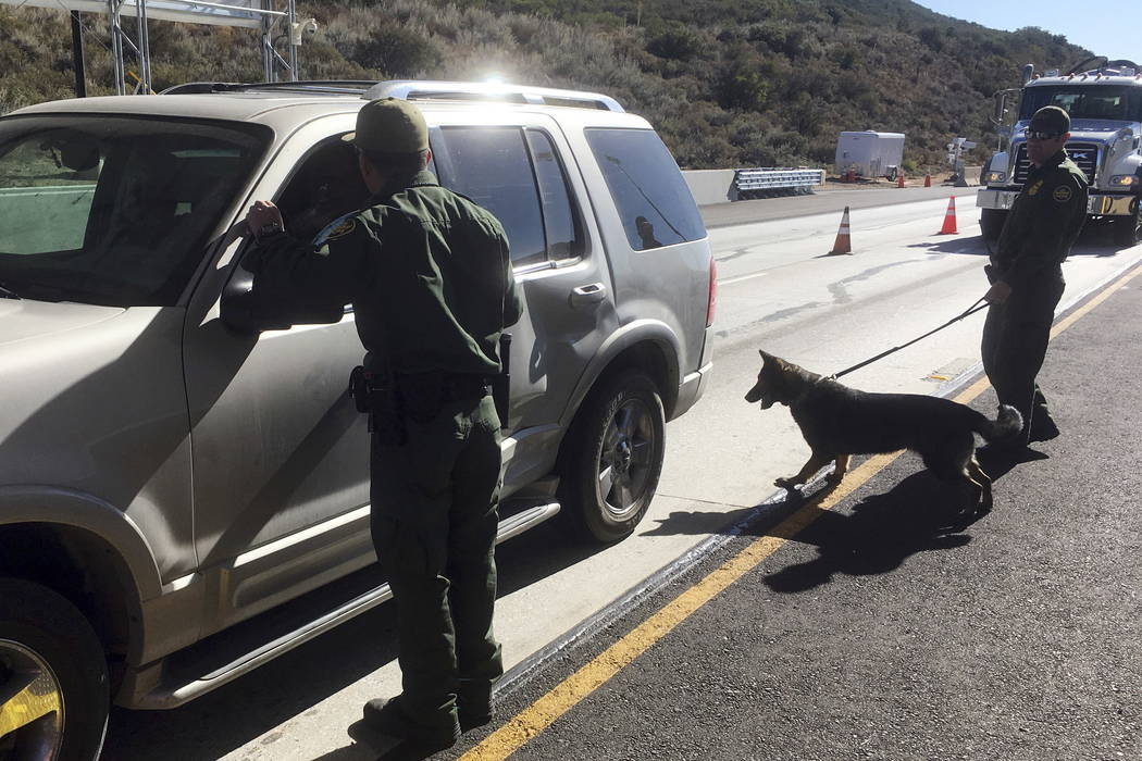 Border patrol agents use a drug sniffing dog to check vehicles at California's Pine Valley checkpoint, on the main route from Arizona to San Diego. (Elliot Spagat/AP Photo)