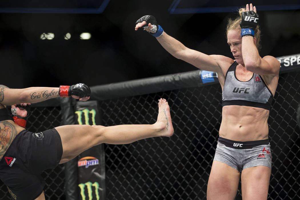 "Holly Holm, right, dodges a kick from Cris ""Cyborg"" Justino in the UFC 219 women's featherweight title bout at T-Mobile Arena in Las Vegas, Saturday, Dec. 30, 2017. Justin ..."