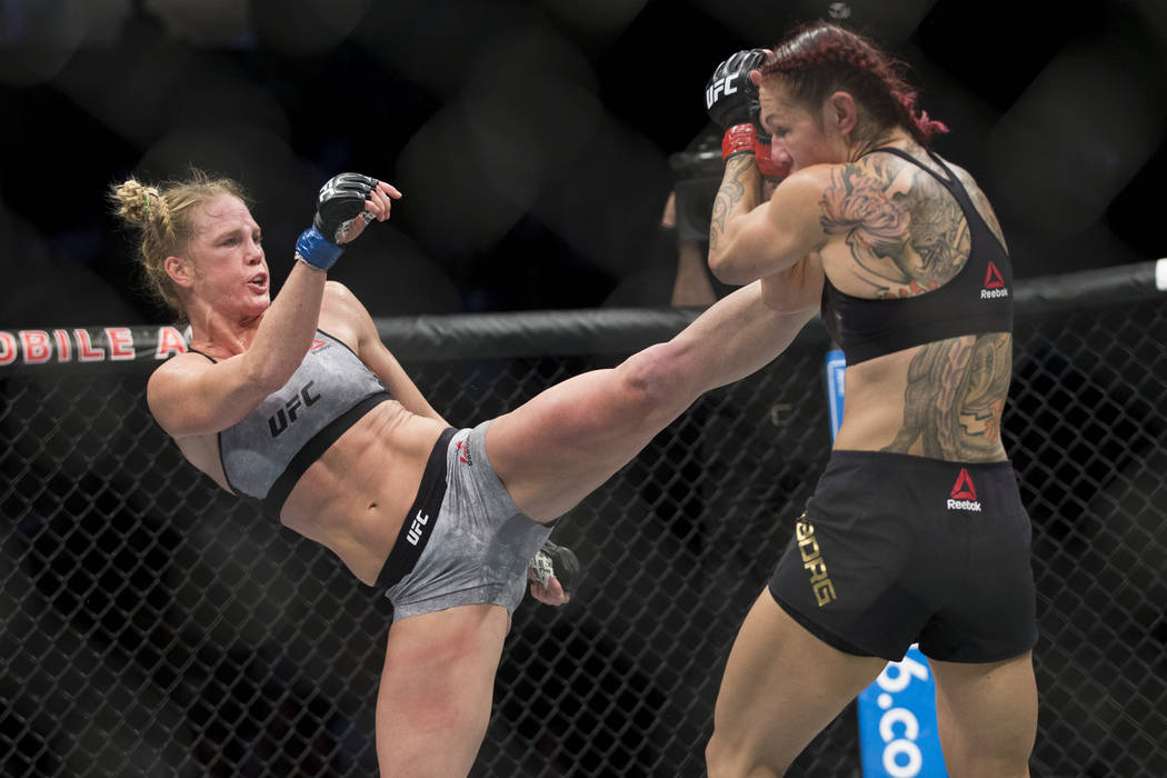"Holly Holm, left, kicks Cris ""Cyborg"" Justino in the UFC 219 women's featherweight title bout at T-Mobile Arena in Las Vegas, Saturday, Dec. 30, 2017. Justino won by unani ..."
