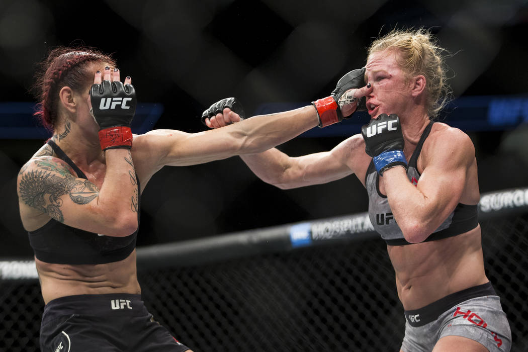 "Cris ""Cyborg"" Justino, left, battles Holly Holm in the UFC 219 women's featherweight title bout at T-Mobile Arena in Las Vegas, Saturday, Dec. 30, 2017. Justino won by una ..."