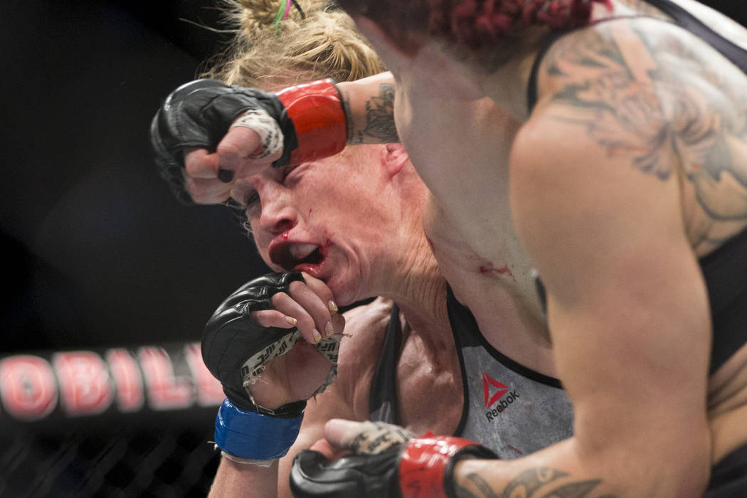"Holly Holm, left, takes a punch from Cris ""Cyborg"" Justino in the UFC 219 women's featherweight title bout at T-Mobile Arena in Las Vegas, Saturday, Dec. 30, 2017. Justino ..."