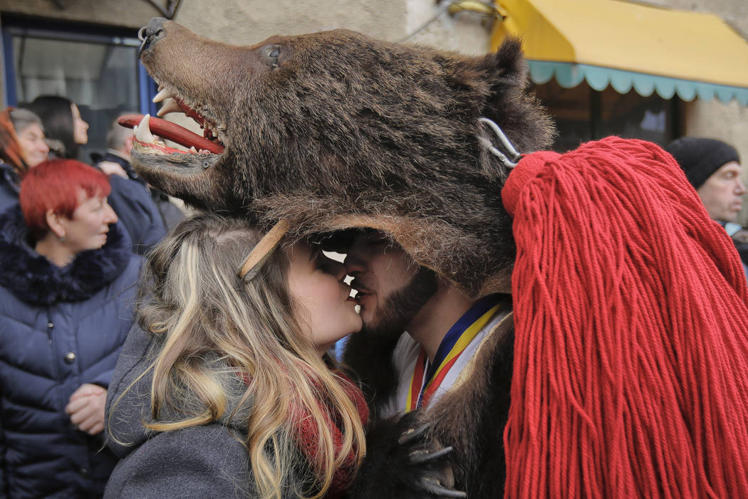 A man wearing a bear fur costume kisses his girlfriend during a parade of new year's rituals in Comanesti, northern Romania, Saturday, Dec. 30, 2017. The tradition, originating in pre-Christian ti ...