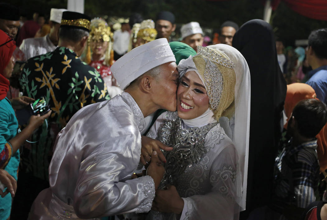 A groom kisses his bride during a mass wedding held in celebration of the New Year in Jakarta, Indonesia, Sunday, Dec. 31, 2017. Hundreds of couples took part in the mass marriage held by the city ...