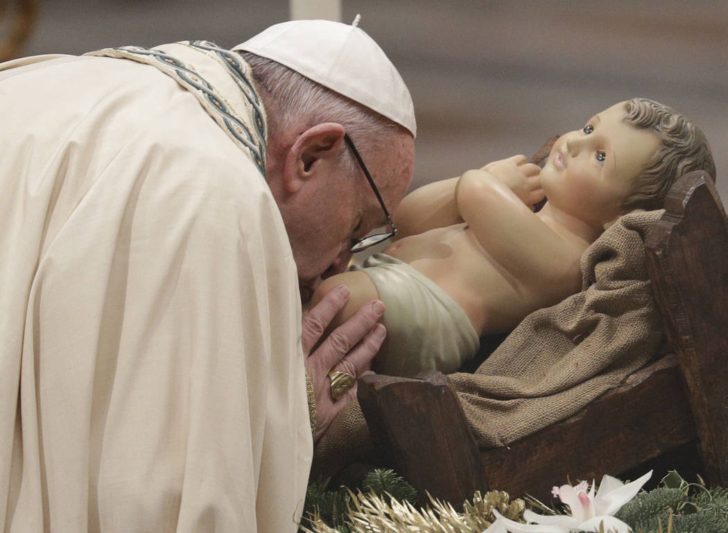 Pope Francis kisses a statue of the Divine Infant as he celebrates a new year's eve vespers Mass in St. Peter's Basilica at the Vatican, Sunday, Dec. 31, 2017. (Andrew Medichini/AP Photo)