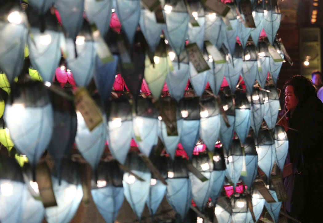 A woman prays in front of lanterns to celebrate the New Year at Jogyesa Buddhist temple in Seoul, South Korea, Sunday, Dec. 31, 2017. (Ahn Young-joon/AP Photo)