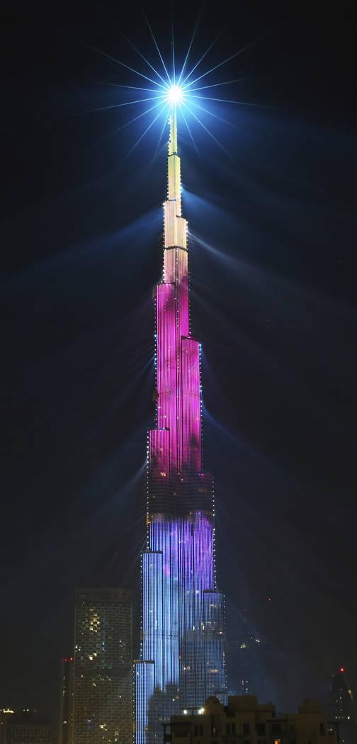 An LED light show illuminates the Burj Khalifa, the world's tallest building, to celebrate the New Year in Dubai, United Arab Emirates, Monday, Jan. 1, 2018. (AP Photo/Jon Gambrell)