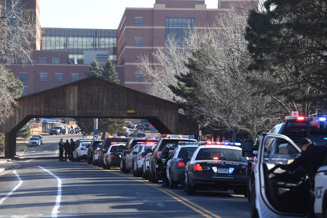 Police officers line up their patrol cars outside of Littleton Adventist Hospital for a procession honoring an officer who was fatally wounded in a domestic incident in a Highlands Ranch apartment ...