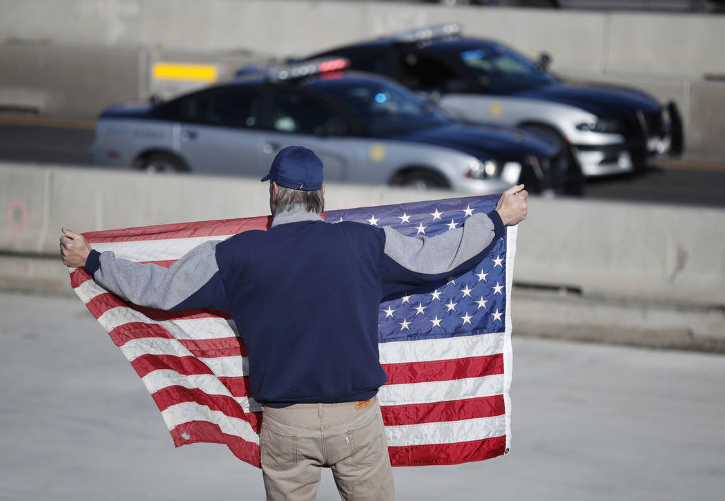 David Morgan of Highlands Ranch, Colo., holds an American flag as a procession of law enforcement vehicles accompany a hearse carrying the body of a sheriff's deputy shot and killed while respondi ...