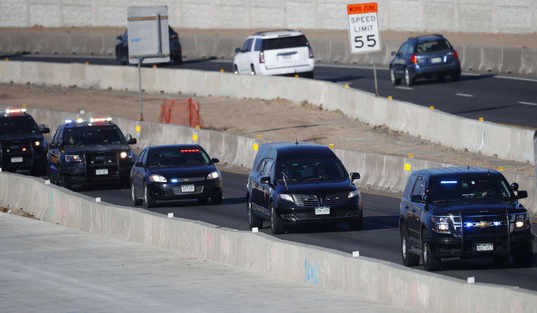 A hearse, second in the procession, carries the body a sheriff's deputy shot and killed while responding to a domestic disturbance Sunday, Dec. 31, 2017, in Highlands Ranch, Colo. (David Zalubowsk ...