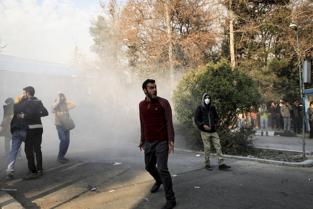 In this photo taken by an individual not employed by the Associated Press and obtained by the AP outside Iran, university students attend a protest inside Tehran University while a smoke grenade i ...