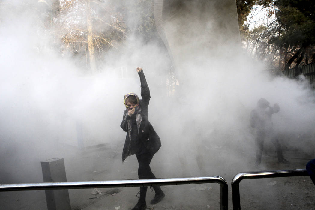 In this photo taken by an individual not employed by the Associated Press and obtained by the AP outside Iran, a university student attends a protest inside Tehran University while a smoke grenade ...